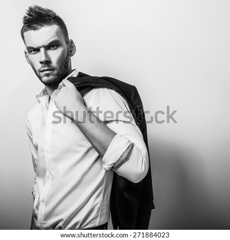 Elegant young handsome serious man in white shirt with jacket. Black-white studio fashion portrait.