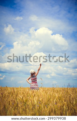 Elegant young lady in candy striped dress with white parasol in field - stock photo