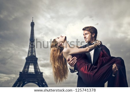 Elegant young lover holding her lover with the Eiffel Tower in the background - stock photo