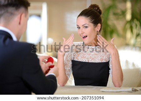 Elegant young man, a declaration of love for his girlfriend, gives the ring sitting in a restaurant - stock photo