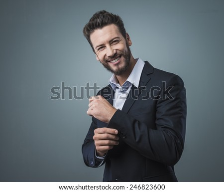 Elegant young man adjusting his jacket and looking at camera - stock photo