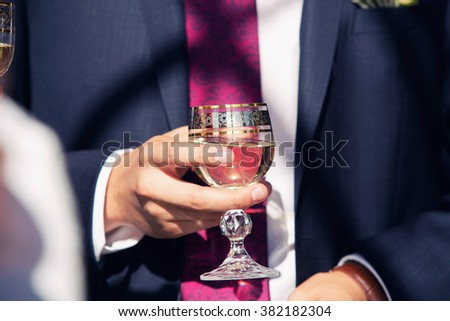 Elegant young man holding a glass of  wine - stock photo