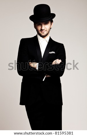 elegant young man in black tuxedo and derby,studio shot - stock photo