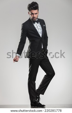 Elegant young man in tuxedo looking at the camera while snapping his finger, full body image. - stock photo
