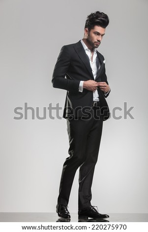 Elegant young man in tuxedo looking away from the camera while closing his jacket, full body image. - stock photo