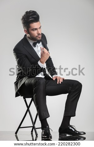 Elegant young man in tuxedo sitting on a stool while snapping his finger, looking away from the camera.  - stock photo