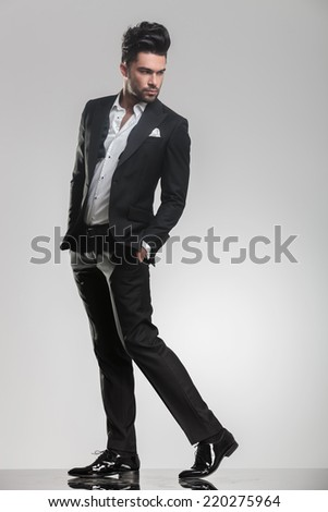 Elegant young man looking away from the camera while walking and holding his hand in pocket - stock photo