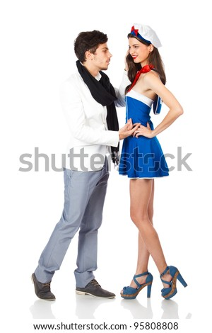 Elegant young man seducing a beautiful attractive woman dressed in sailor uniform. Isolated on white background. High resolution studio image - stock photo