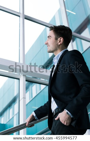 Elegant young man smiling and looking up while going down the stairs next to a glass wall of a modern building