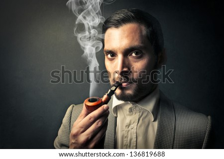 elegant young man smokes a pipe - stock photo