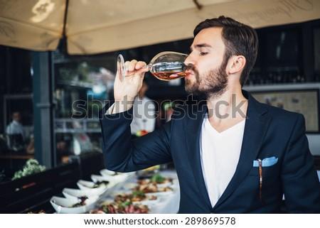 Elegant young man tasting wine - stock photo