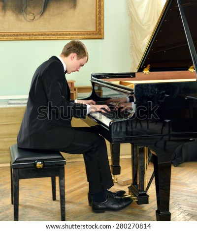 Elegant young pianist plays on black grand piano - stock photo