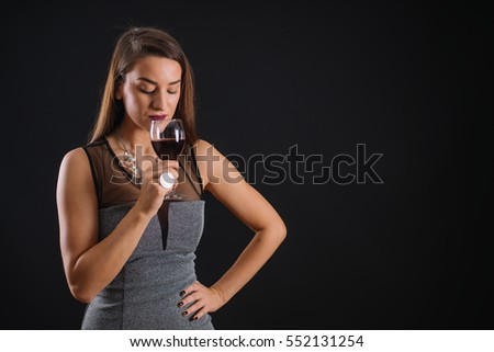 Elegant young woman celebrating with a glass of wine