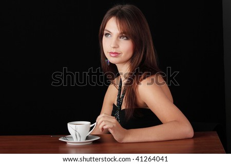Elegant young woman drinking coffee, isolated on black - stock photo