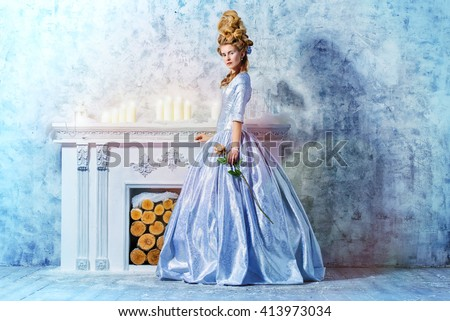 Elegant young woman in a lush white medieval dress with hair in the style of the Renaissance. Beautiful Ice Queen in her snow palace.   - stock photo