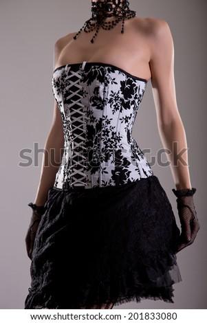 Elegant young woman in black and white corset, studio shot  - stock photo