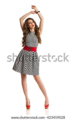 Elegant young woman in black and white striped dress and high heels posing with arms raised and looking at camera. Full length studio shot isolated on white. - stock photo