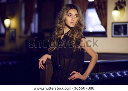 Elegant young woman in black evening dress posing in interior. Fashion style portrait of a beautiful girl in interior.