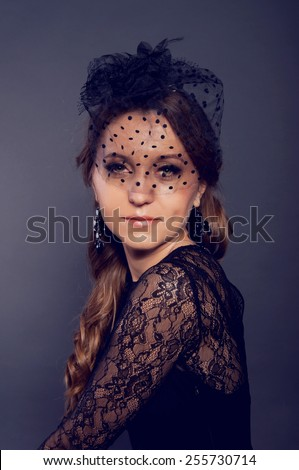 Elegant young woman in black lace dress and black veil hat with long curly hair. Retro style.