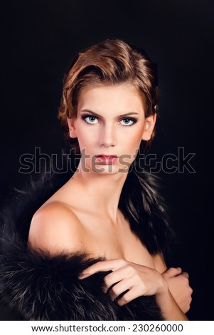 Elegant young woman in black lingerie with fur boa posing at studio on black background