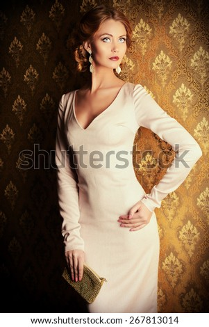 Elegant young woman in  evening dress posing in vintage interior. Jewellery.  Fashion shot. - stock photo