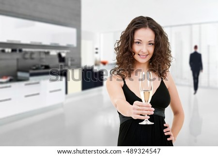 Elegant young woman in her luxury living room holding a glass of champagne and invite you to join