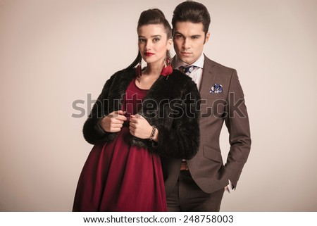 Elegant young woman leaning on her lover while he is looking at the camera with his hands in pockets.