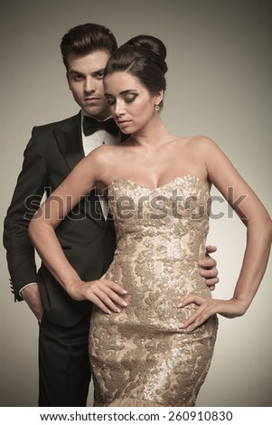 Elegant young woman looking down while her lover is holding her. - stock photo