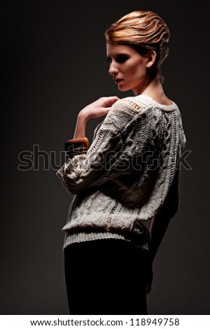 elegant young woman over dark background - stock photo