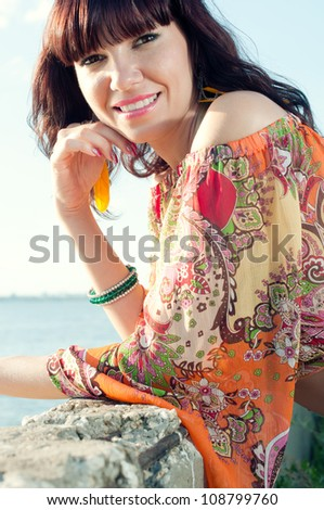 Elegant young woman relaxing outdoors, smiling and looking at camera - stock photo