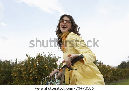 Elegant young woman riding a motorbike in an orange grove. - stock photo