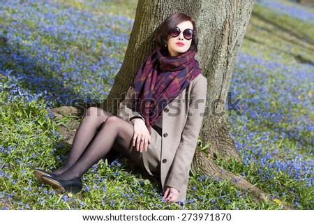 Elegant young woman sitting under the tree on the grass with flowers. - stock photo