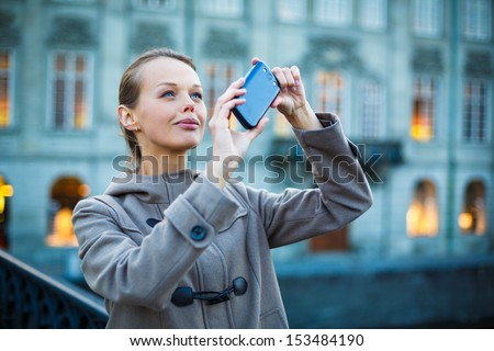 Elegant, young woman taking a photo with her cell phone camera while traveling (shallow DOF; color toned image) - stock photo