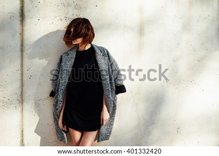 Elegant young woman wearing in a black blank t-shirt posing against a background  of concrete wall - stock photo