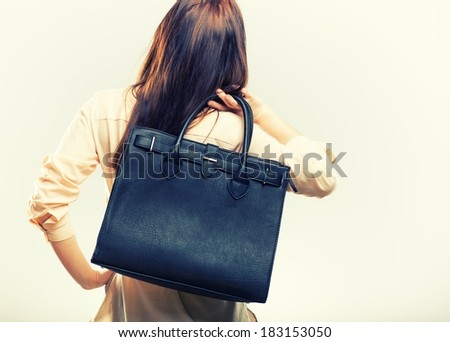 Elegant young woman with black leather bag, back view - stock photo