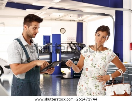 Elegant young woman with disgust on face handing car key to car mechanic. - stock photo