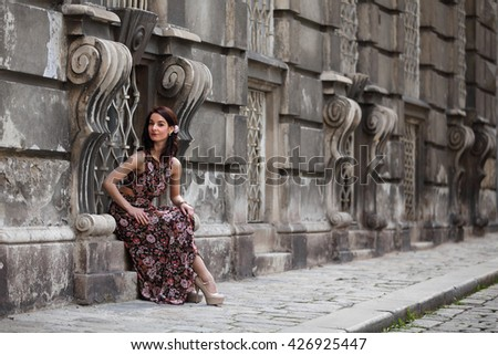 Elegant young woman with summer dress and high heels sitting in the window of a palace