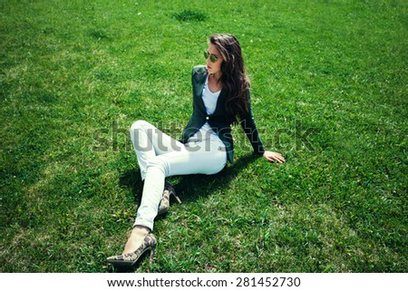 elegant young woman with sunglasses, green jacket,  white pants and high heel shoes sit on grass in park, full body shot - stock photo