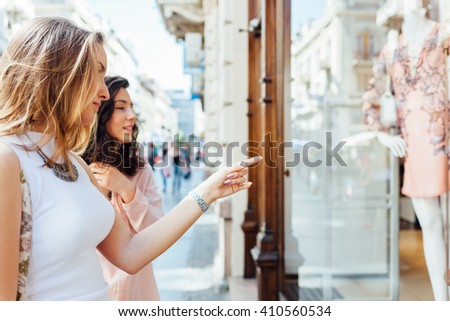 Elegant young women looking at boutique showcase - stock photo