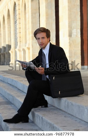 elegant young working man sitting on stairs - stock photo