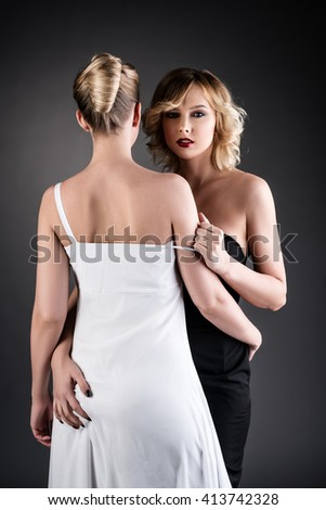 Elegantly dressed blondes hugging at camera - stock photo