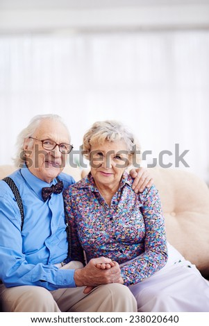 Elegantly dressed retired couple looking at camera - stock photo