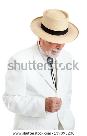 Elegantly dressed senior man from the American South or the Islands, wearing a white suit, string tie, and straw Panama hat.  Isolated on white. - stock photo
