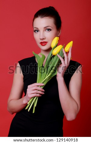 Elegantly dressed young girl holding a bouquet of yellow flowers in spring - stock photo