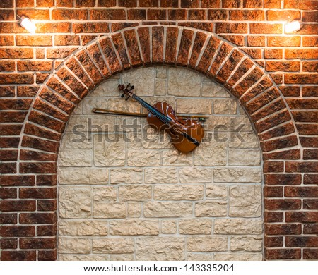 Element of the interior stone arch with a violin on a wall - stock photo