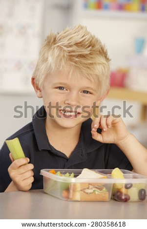 Elementary Age Schoolboy Eating Healthy Packed Lunch In Class - stock photo