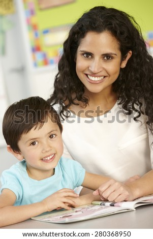 Elementary Age Schoolgirl Reading Book In Class With Teacher - stock photo