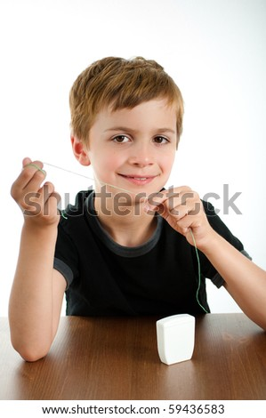 Elementary Age Student Learning How to Use Dental Floss - stock photo