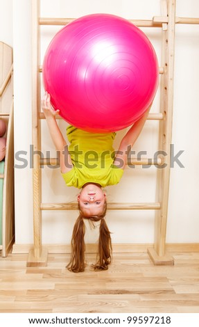 Elementary aged girl hanging on wooden wall bars with a large gymnastic ball - stock photo