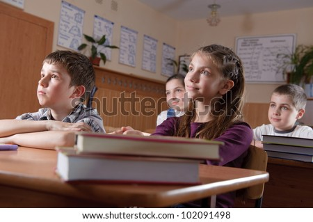 Elementary aged pupils listen to the teacher - stock photo